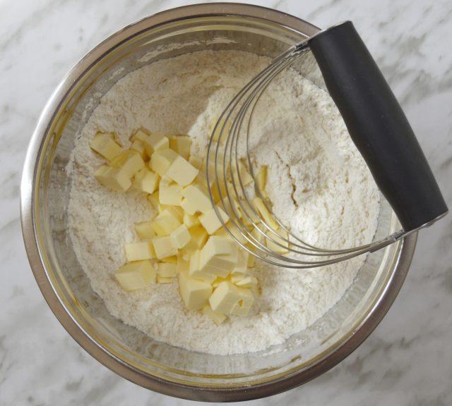 Añadiendo la mantequilla en trozos. Mezclador de masas. Scones. Aroma de chocolate