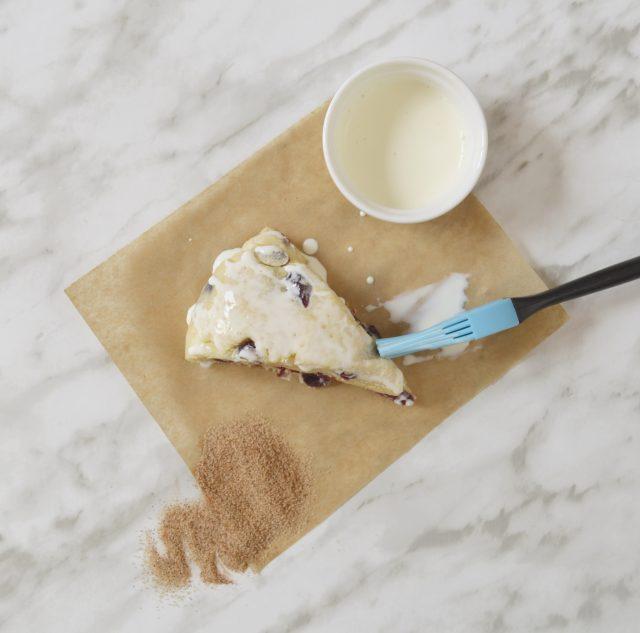 Pincelando los scones con la nata. Espolvoreando el azúcar con canela. Aroma de chocolate