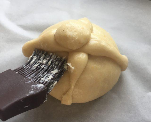 Pincelando el pan de muerto con mantequilla. Aroma de chocolate